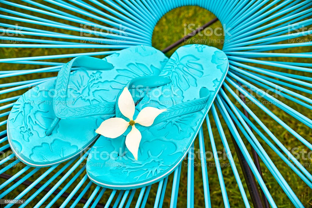 Turquoise blue garden chair and flip flops, green lawn background
