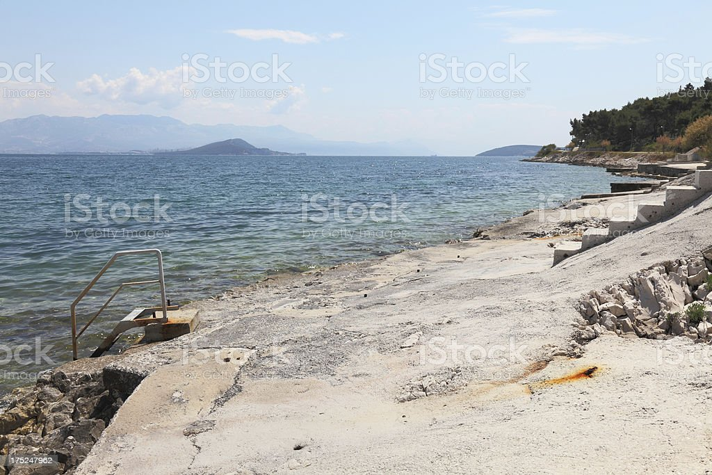 turquoise blue mediterranean beach view with steps Trogir Croatia royalty-free stock photo