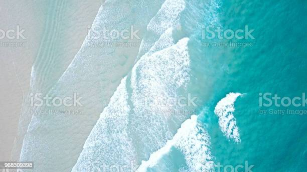 Photo of Turquoise blue ocean water white wash crashing on shoreline sand beach drone aerial from above