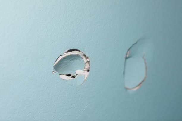家中綠松石藍色牆,在薄石上有兩個洞 - 毆打 個照片及圖片檔