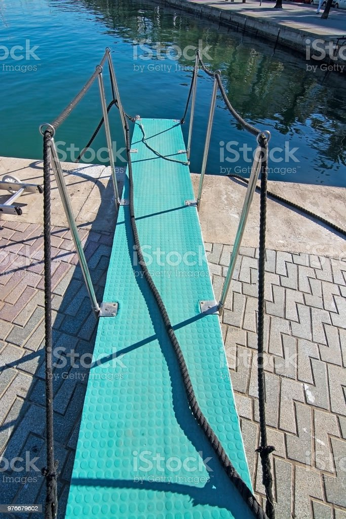 Turquoise board bridge rope and no boat stock photo