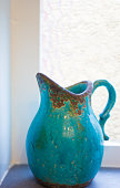 Turquoise Ceramic Pitcher (Close-Up) in Window. Copy space available.
