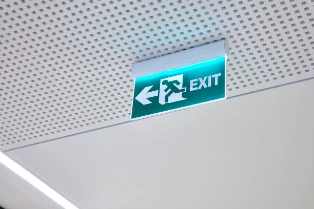 turquoise color fluorescent exit sign - exit sign stock photos and pictures