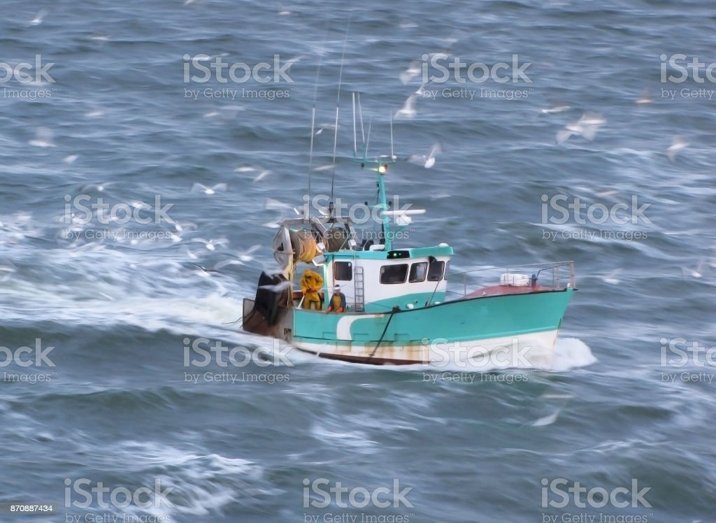 Turquoise Colored Fishing Boat in Motion on Sea stock photo