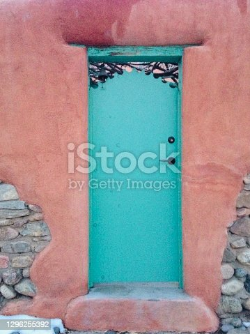 Closeup photo of a vibrant turquoise front door with a black metal decorative trim, black door handle and keyhole on the front wall of a traditional Adobe house in the old area of Santa Fe, New Mexico. The original stones underneath the Adobe can be seen on two sections where the Adobe has been removed. Snow patches lie in the ground