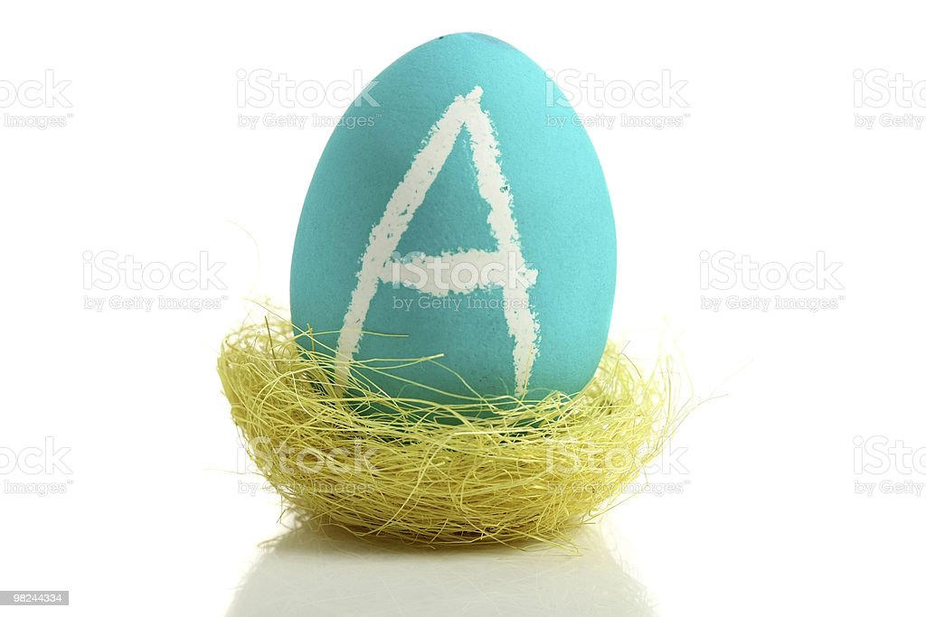 Turquoise easter egg with letter in nest royalty-free stock photo