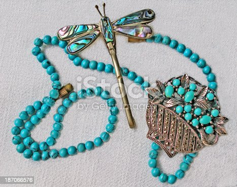 Turquoise gem jewels arrangement on textured fabric background. String,butterfly,silver basket with turquoise flowers,brooch.