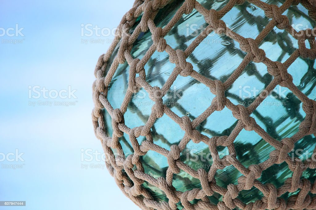 Turquoise glass sphere tied up with nautical rope & knots. stock photo