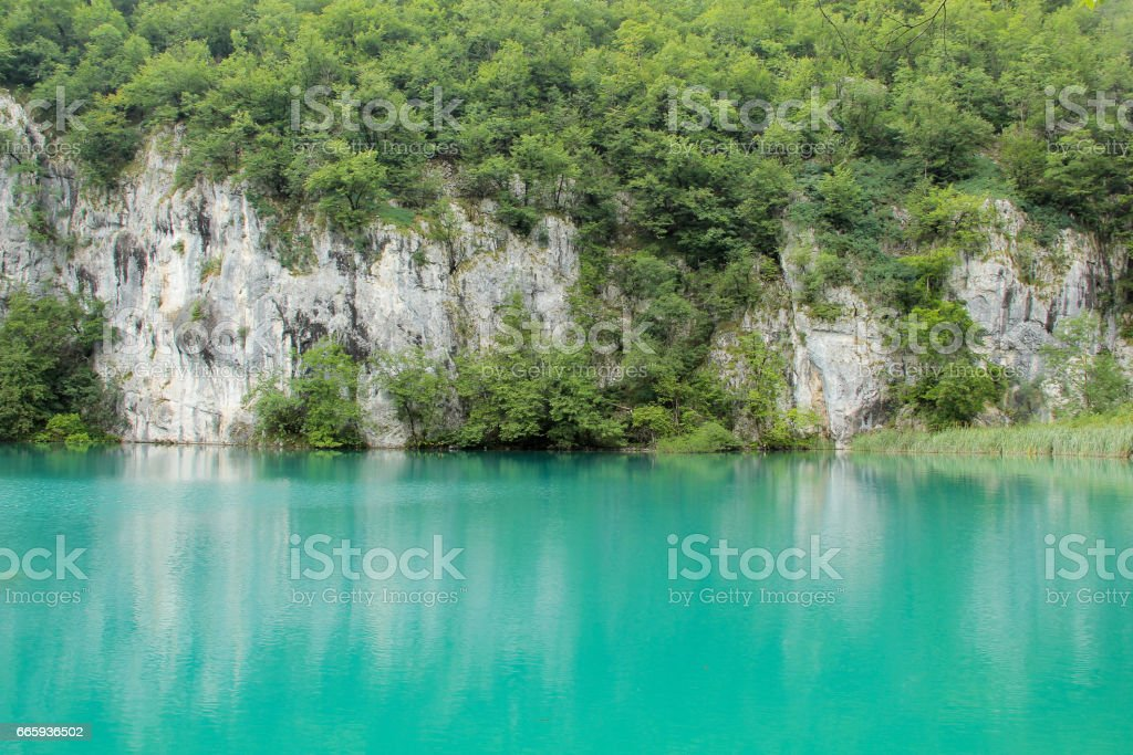 Turquoise lake surrounded by rocky wall in Plitvice lakes, Croatia foto stock royalty-free