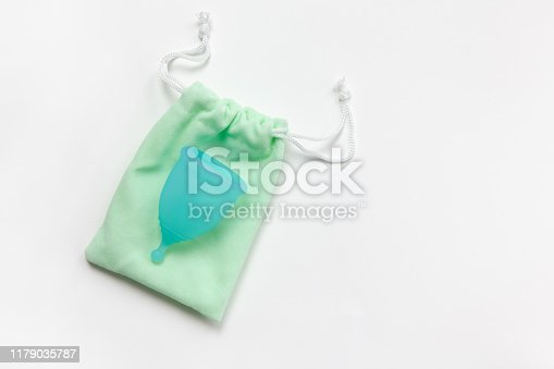 istock Turquoise menstrual cup on green small bag on white background. Concept zero waste, savings, minimalism, these days. Feminine hygiene product, flat lay, copy space. Horizontal 1179035787