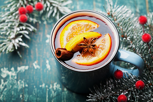Turquoise mug of christmas mulled wine or gluhwein with spices and orange slices on wooden teal table.