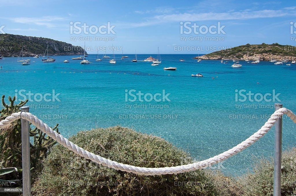 Turquoise ocean bay with boats and rope fence royalty-free stock photo