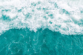 Turquoise olive green gentle breeze ocean wave during summer tide, abstract sea nature background