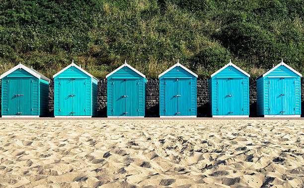 Turquoise painted wooden beach huts in Bournemouth Beach huts at Bournemouth, Dorset, UK. beach hut stock pictures, royalty-free photos & images