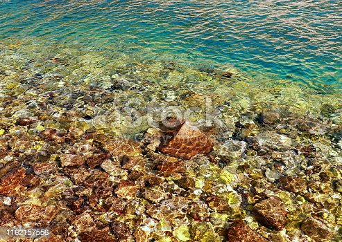 959508862 istock photo Turquoise shallow water surface and rocks stones on sea floor 1162157556
