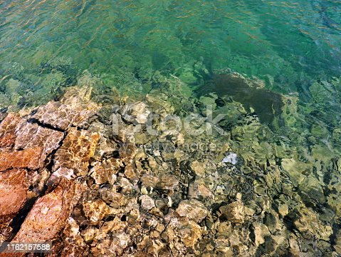 959508862 istock photo Turquoise shallow water surface and rocks stones on sea floor 1162157588