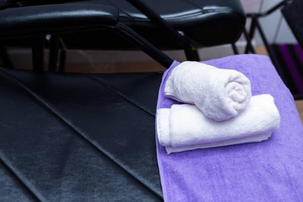 türkis spa handtücher stapeln sich auf sesseln mit waschständern im friseursalon. - türkise haare stock-fotos und bilder