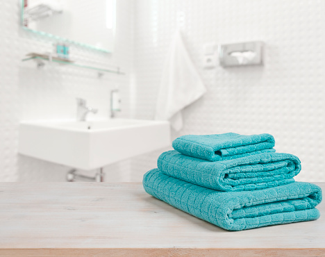618327092 istock photo Turquoise spa towels pile on wood over blurred bathroom background 637898762
