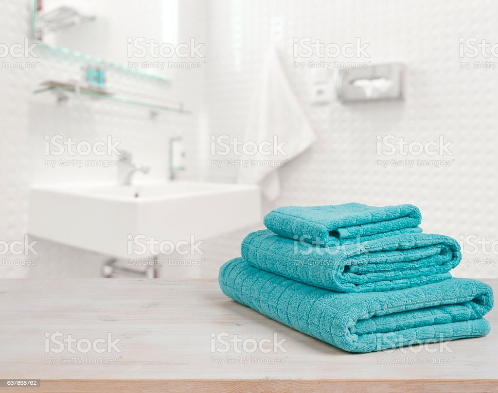 Turquoise spa towels pile on wood over blurred bathroom background stock photo