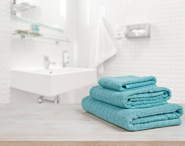 turquoise spa towels pile on wood over blurred bathroom background - 수건 뉴스 사진 이미지