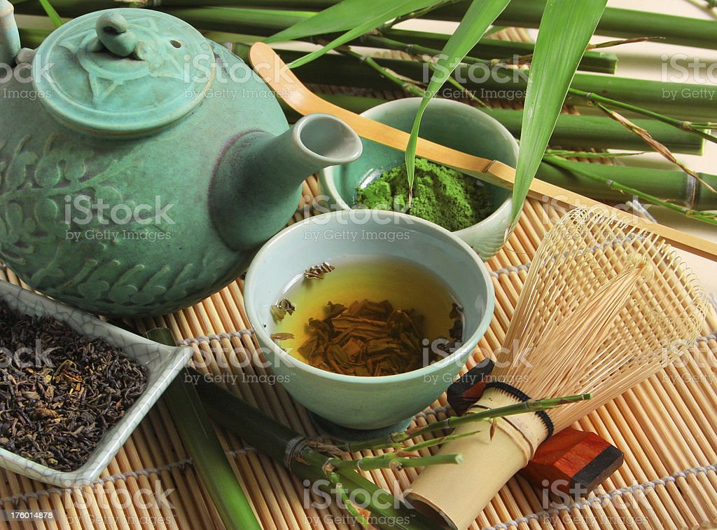 Turquoise teapot and mug of green tea with bamboo stock photo