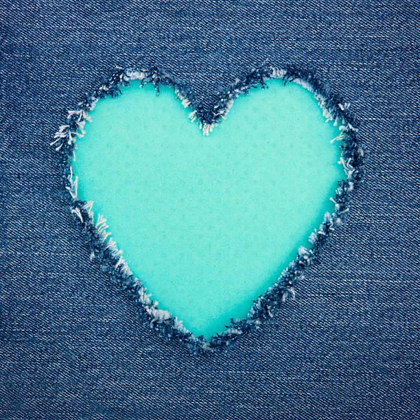 Turquoise vintage heart on blue denim fabric stock photo