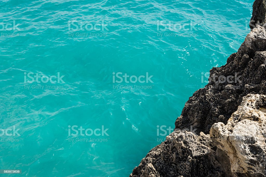 turquoise water at a cliff of lava stone stock photo