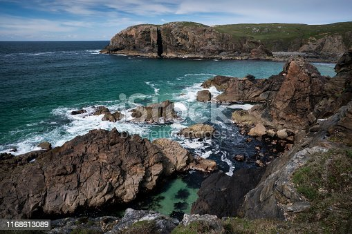 Dalbeg Beach, Dail Beag, is a hidden gem of turquoise waters crashing into rocks and disappearing into the expansive sandy beach in a picturesque bay on the Atlantic Ocean on the northwest side of the Isle of Lewis in the Outer Hebrides, Scotland, UK, Europe
