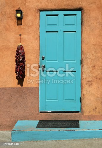 Turquoise wooden door a chili ristra and an adobe wall on a house