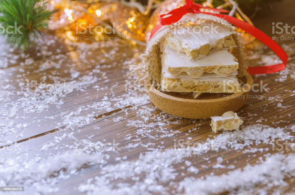 Turron, typical Christmas sweet in Spain. Almond nougat on red napkin  on dark wooden background with Christmas decoration, snow and fir tree.Copy space. stock photo