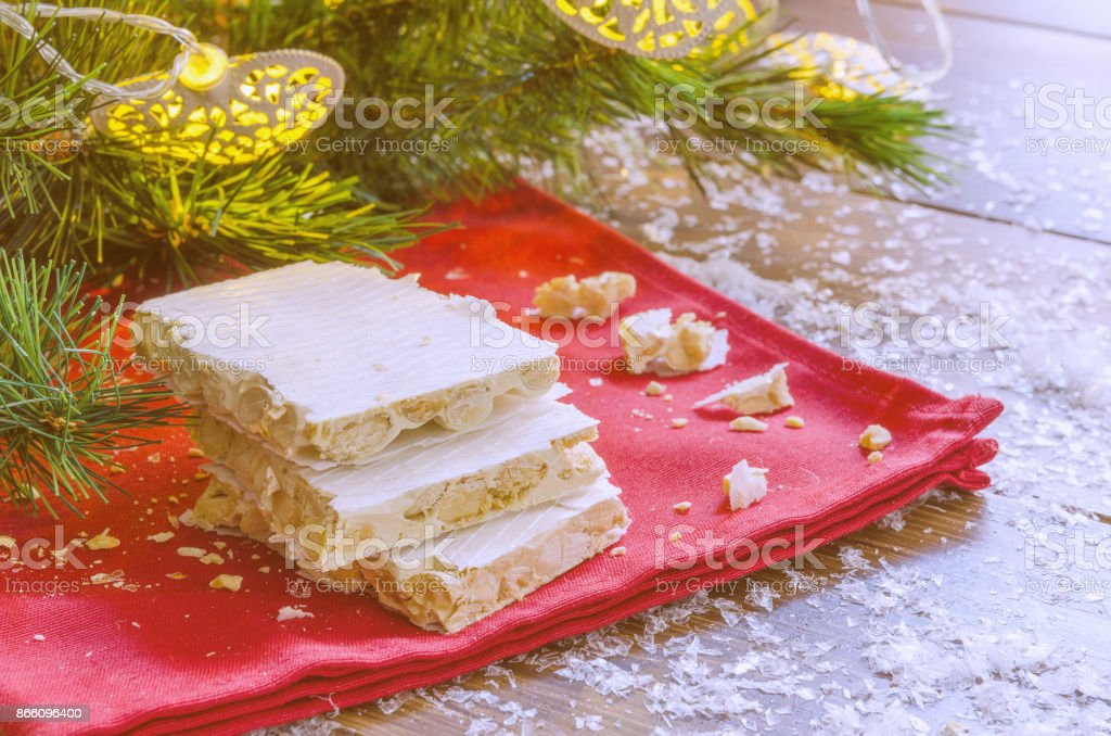 Turron, typical Christmas sweet in Spain. Almond nougat on red napkin  on dark wooden background with Christmas decoration, snow and fir tree. stock photo