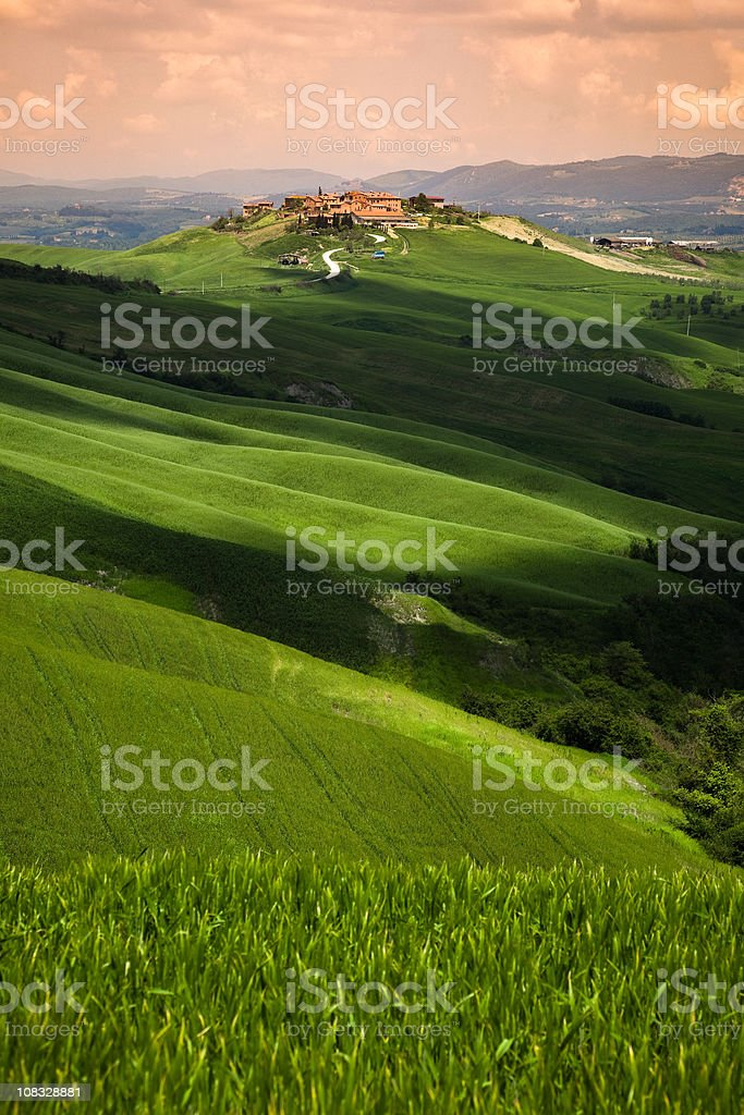 Tuscan Village Surrounded By Green Landscape At Sunset royalty-free stock photo