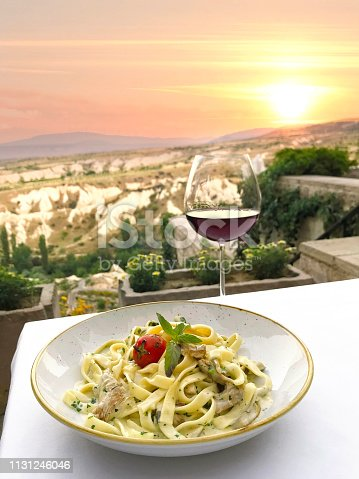 Delicious fettuchini pasta dish on a restaurant table with sunset view in Tuscany