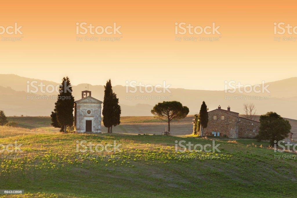 Tuscany landscape at sunrise with a little chapel of Madonna di Vitaleta, Italy. stock photo