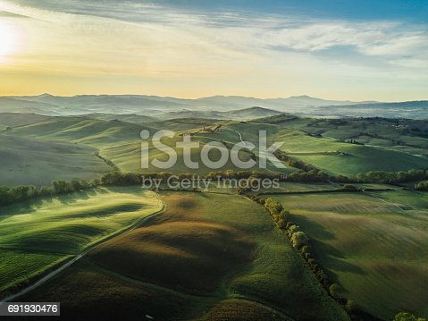 Tuscany landscape at sunrise with low fog.
