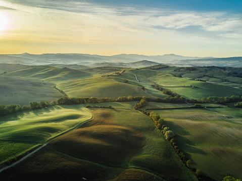 Tuscany landscape at sunrise with low fog.