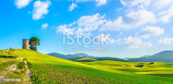 Tuscany, Maremma countryside landscape. Old windmill and trees on top of the hill. Bibbona, Livorno, Italy.