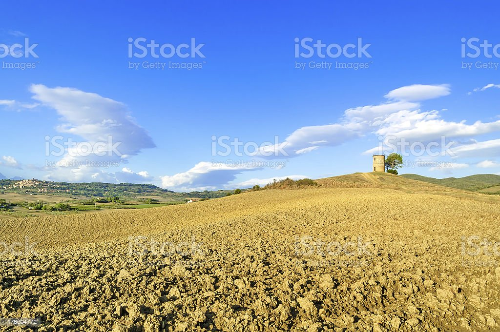 Tuscany, Maremma landscape. Rural tower, plowed field, village on background. stock photo