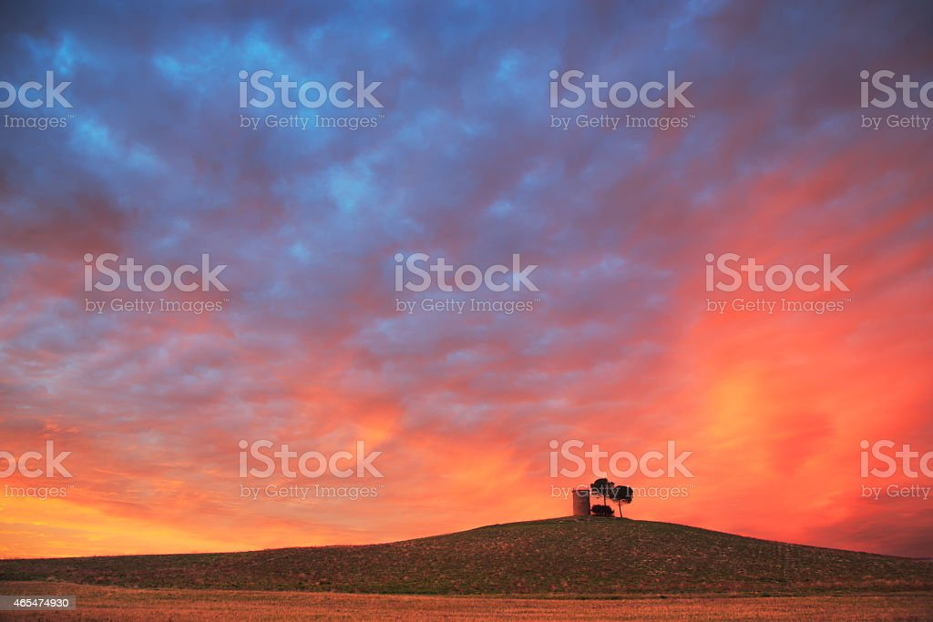 Tuscany, Maremma red sunset landscape. Rural tower, tree on h stock photo