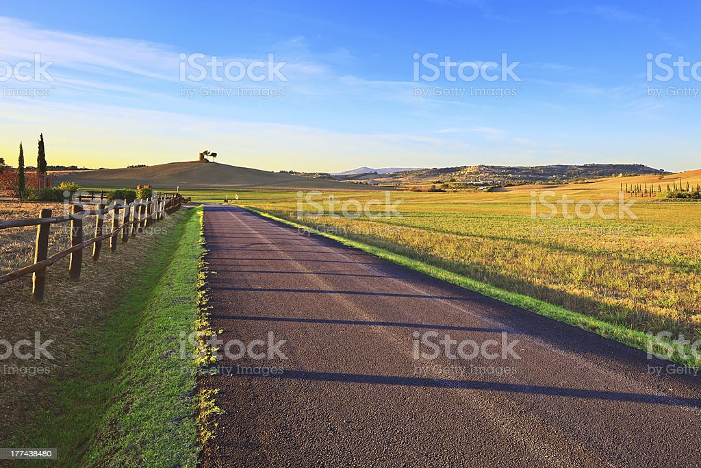 Tuscany, Maremma sunset landscape. Rural road and green field. Italy. stock photo