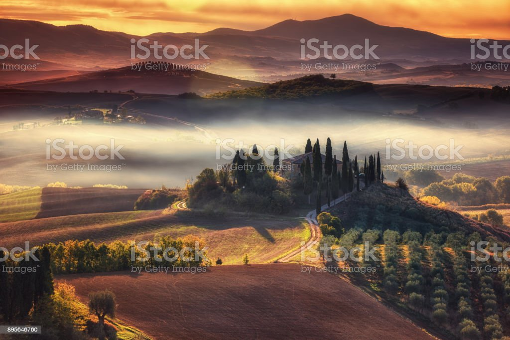 Tuscany, panoramic landscape with famous farmhouse rolling hills and valleys in beautiful golden morning light at sunrise in autumn, Val d'Orcia, Italy stock photo