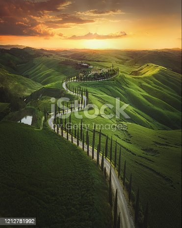 Magical sunset and rural landscape view of Picturesque agrotourism with characterized green top hill farms of olive groves and vineyards typical curved road with cypress at Crete Senesi in Toscana, Italia, Europe
