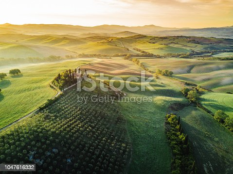 Tuscany's valley in Val d'Orcia at sunrise from aerial point of view