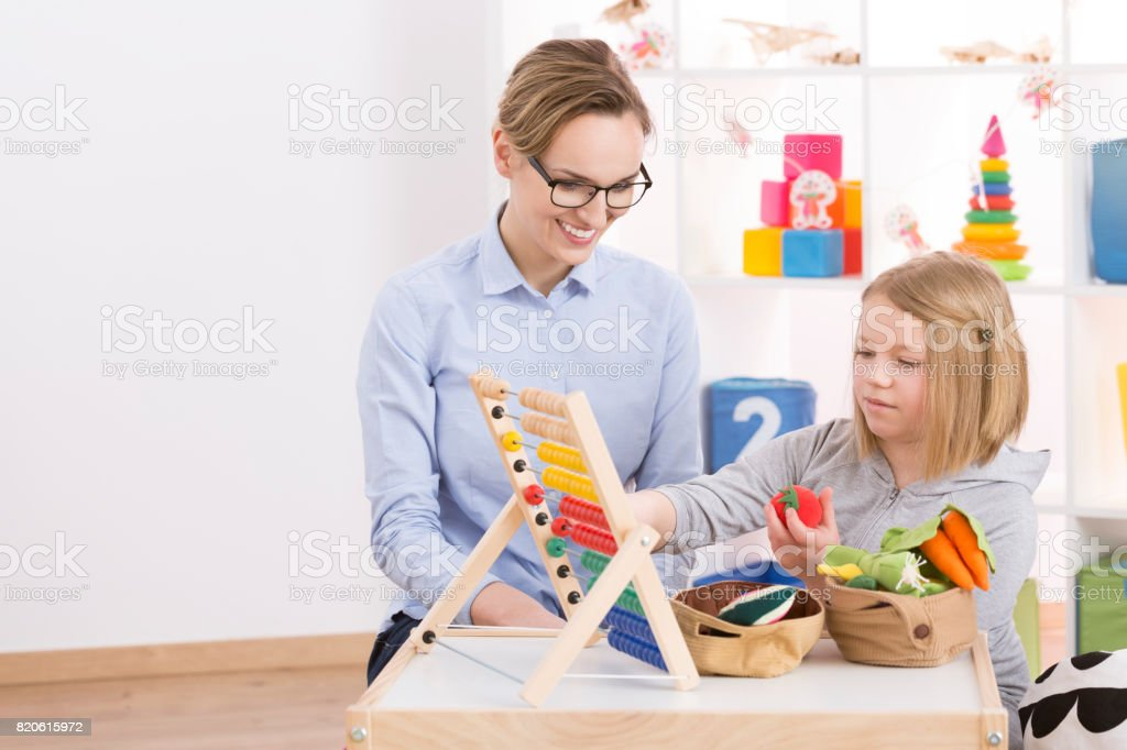 Tutor and girl counting with abacus stock photo