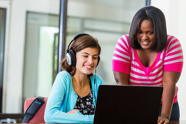 Tutor assisting preteen girl with homework on laptop Tutor assisting preteen girl with homework on laptop cute middle school girls stock pictures, royalty-free photos & images