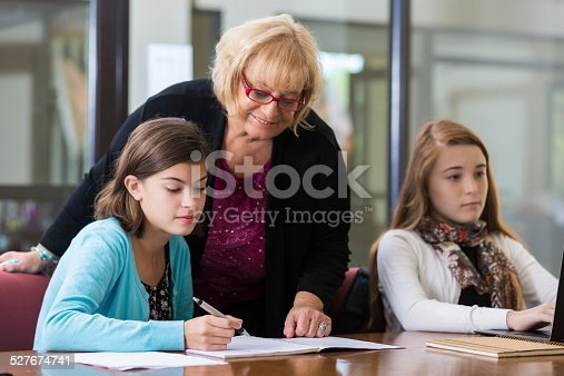 641755828 istock photo Tutor assisting preteen students during after school program 527674741