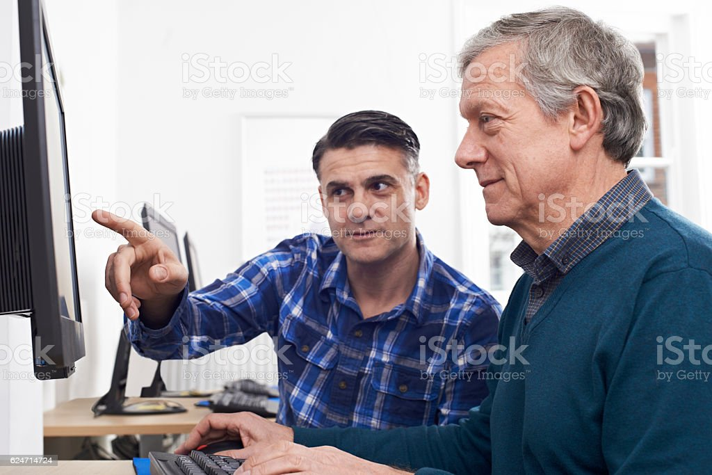 Tutor Helping Mature Man In Computer Class - foto de acervo