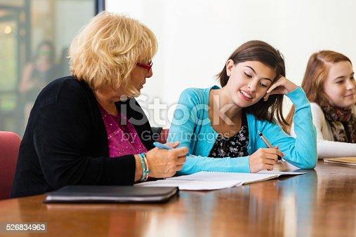 641755828 istock photo Tutor teaching preteen students during after school homework program 526834963