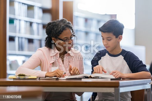 Encouraging female tutor works with preteen boy in the campus library. They are looking at a textbook.