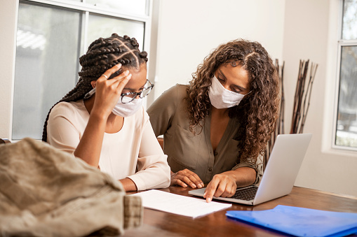 A African American student getting tutored at home during the cover-19 outbreak.